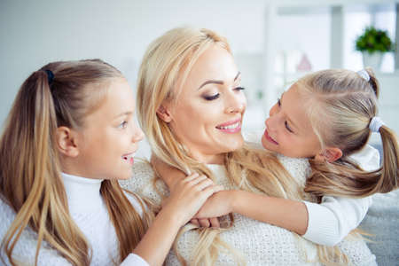 Close-up portrait of three nice cute lovely sweet charming attractive winsome cheerful cheery people pre-teen girls mom mommy in light white interior room indoors