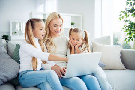 Portrait of three nice-looking cute pretty lovely attractive charming cheerful people pre-teen girls mom sitting on divan making video calls in light white interior room hotel indoors Stock Photo