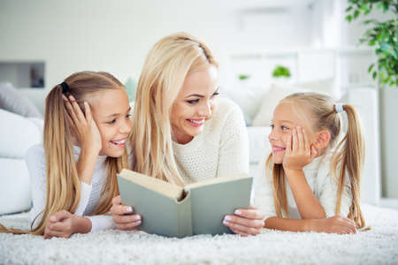 Portrait of three nice cute pretty lovely sweet adorable attractive charming cheerful people pre-teen girls mom mum mommy lying on carpet reading poems in light white interior room indoors