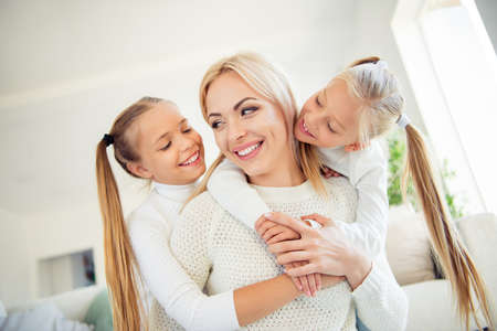 Close-up low angle view portrait of nice cute lovely dreamy sweet gorgeous winsome attractive cheerful mama piggybacking pre-teen girls spending free time weekend in light white room Stock Photo