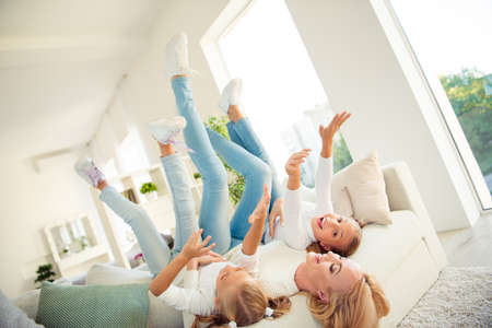Profile side view of nice cute attractive charming lovely crazy careless carefree cheerful people rejoicing upside-down having fun on divan in modern light white interior room indoors Stock Photo