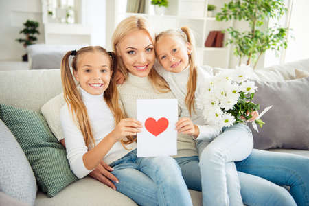 Portrait of nice cute adorable lovely winsome sweet charming attractive cheerful mama pre-teen girls sitting on divan holding post card daydream vacation weekend in light white room