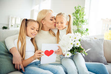 Portrait of nice cute lovely winsome sweet charming attractive cheerful cheery mom pre-teen girls sitting on divan reading post card daydream in light white room