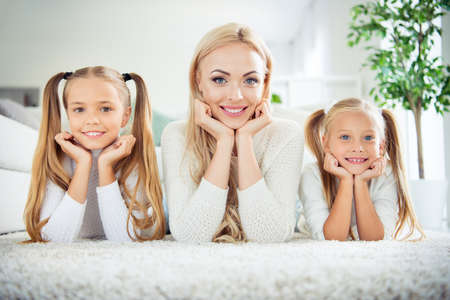 Portrait of three nice cute lovely attractive winsome cheerful positive people pre-teen girls mom mum mommy lying resting on carpet in light white interior room indoors