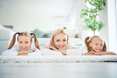 Portrait of three nice cute lovely adorable attractive charming cheerful cheery people pre-teen girls mom mum mommy lying on carpet in light white interior room house indoors