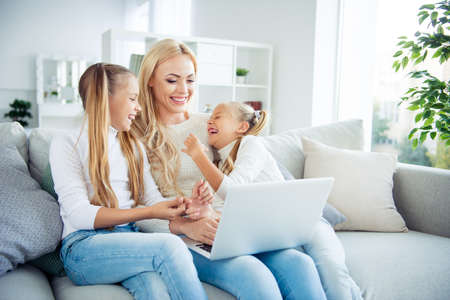 Portrait of three nice-looking cute pretty lovely attractive cheerful people pre-teen girls mom sitting on divan making video call w-fi in light white interior room hotel indoors Zdjęcie Seryjne