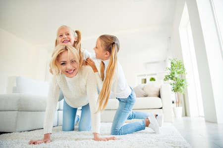 Low angle view of nice cute lovely dreamy sweet charming attractive cheerful cheery mama on carpet carrying piggybacking pre-teen girls spending time vacation weekend having fun in light white room