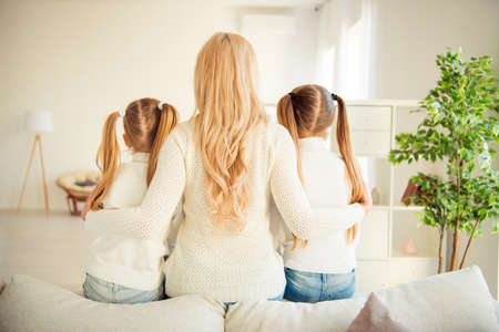 Rear back behind view of nice adorable blonde stylish trendy slim people kind tender mom mommy mum girls sitting hugging in modern light white interior room indoors