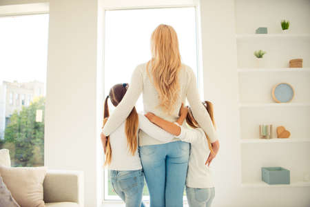 Rear back behind view of nice stylish trendy slim people mom mum girls hugging in front of window in light white interior room hotel indoors Foto de archivo