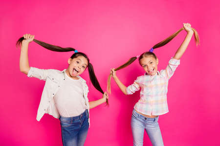 Close up photo two pretty little age girls holiday having fun funky childish glad tongue out mouth hairdo up in air wearing casual jeans denim shirts isolated rose bright vivid vibrant background