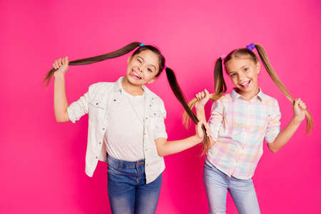 Close up photo two pretty little age girls holiday having fun childish glad tongue out mouth blinking playing wearing casual jeans denim checkered plaid shirts isolated rose vivid vibrant background 写真素材