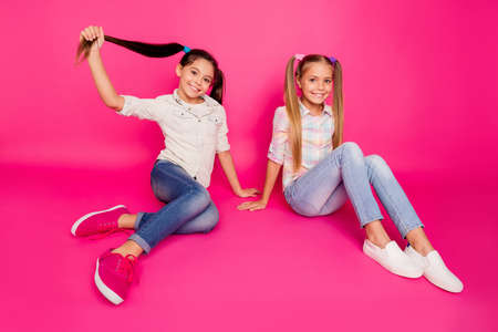 Close up photo two little age she her girls leaning hands arms best friends sit floor optimistic smile winners wearing casual jeans denim checkered plaid shirts isolated rose vibrant vivid background Foto de archivo