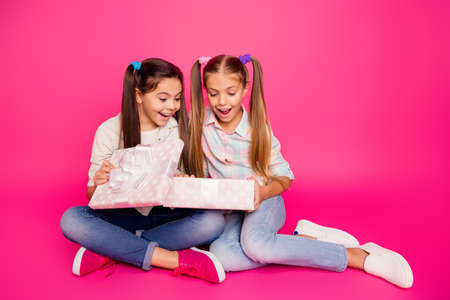 Close up photo two little age she her girls hands arms large giftbox best friends sit floor wear casual jeans denim checkered plaid shirts isolated rose vibrant vivid background