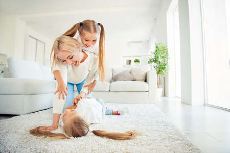 Nice cute crazy lovely dreamy sweet adorable attractive cheerful funny mama on carpet carrying piggybacking pre-teen girl playing game fooling having fun in light white room