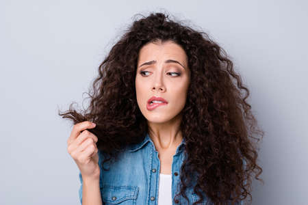Close-up portrait of her she nice attractive worried nervous wavy-haired girl holding looking at dry wealth curls thinking about solution repair anti loss isolated over gray pastel background
