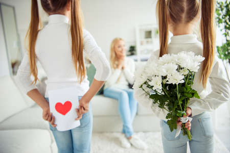 Nice lovely adorable attractive charming cheerful positive cheery pre-teen girls prepared hiding gifts for mom mommy mum sitting on divan in light white interior room indoors Stockfoto