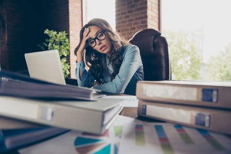 Cerrar una foto hermosa ella, su señora de negocios, cansada de la contabilidad, el tiempo de ejecución, los últimos minutos, segundos, hasta que el jefe jefe regrese, los papeles del desorden, sostienen la cabeza, se sientan en la silla de la oficina, vistiendo un traje formal