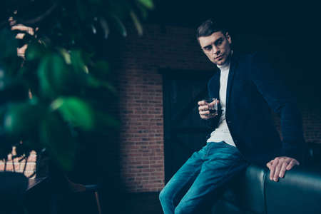 Profile side view portrait of his he attractive handsome stylish trendy minded guy top management career development question drinking beverage at industrial loft interior workplace workspace Reklamní fotografie