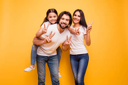 Portrait of nice cute sweet lovely attractive charming cheerful dreamy funny people mom dad pre-teen girl showing v-sign isolated over shine vivid pastel yellow background Archivio Fotografico - 117892598