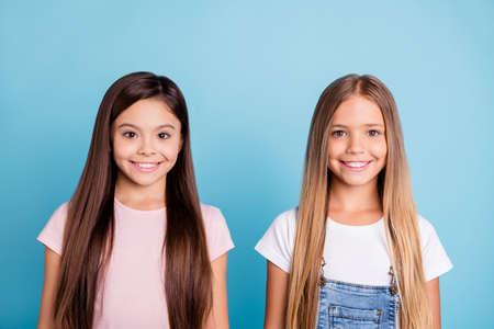 Nahaufnahmeporträt von zwei gut aussehenden süßen zarten attraktiven schönen fröhlichen glatthaarigen Mädchengeschwistern einzeln auf blauem pastellfarbenem Hintergrund