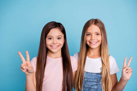 Close-up portrait of two people nice-looking lovely sweet tender attractive beautiful cheerful straight-haired girls siblings showing v-sign isolated over blue pastel background