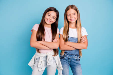 Portrait of nice-looking cute lovely sweet adorable well-groomed attractive cheerful cheery straight-haired brunette blonde girls siblings folded arms isolated over blue pastel background