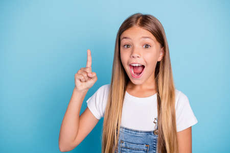 Close-up portrait of her she nice cute lovely smart clever intelligent attractive funny straight-haired blonde pre-teen girl pointing up opened mouth isolated on blue pastel background