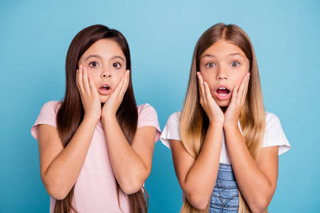 Close-up portrait of two people nice cute attractive charming scared frightened funny straight-haired pre-teen girls touching cheeks scary news isolated over blue pastel background