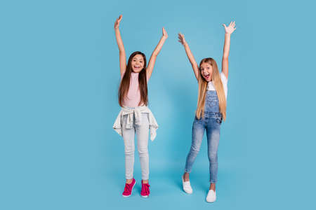 Full length body size view portrait of two people nice lovely attractive cheerful crazy straight-haired pre-teen girls siblings raising hands up great news isolated on blue turquoise background Stock Photo