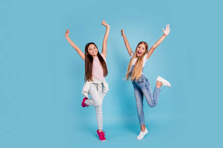 Full length body size view portrait of two people nice attractive cheerful crazy funny funky playful straight-haired pre-teen girls raising hands up chill out rest relax isolated on blue background Stock Photo
