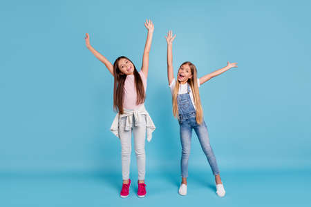 Full length body size view portrait of two people nice lovely attractive cheerful straight-haired pre-teen girls raising hands up chill out rest relax isolated on blue turquoise background