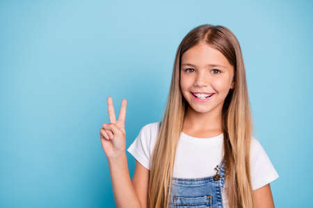 Close-up portrait of her she nice cute lovely sweet charming winsome attractive cheerful cheery straight-haired blonde pre-teen girl showing v-sign isolated on blue pastel background