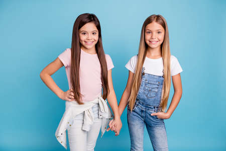 Portrait of two people nice cute lovely sweet charming dreamy attractive cheerful cheery straight-haired pre-teen girls siblings holding hands isolated over blue pastel background