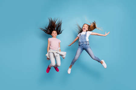 Full length body size view of two people nice-looking crazy attractive cheerful carefree careless straight-haired pre-teen girls having fun great spare free time overjoy isolated on blue background
