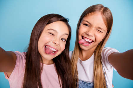 Close up photo two pretty little age girls holiday having fun funky tongue out of mouth make take selfies long pretty hair wearing casual jeans denim t-shirts isolated on blue bright background