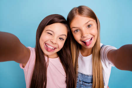 Close up photo two pretty little age girls holiday having fun funky childish glad tongue out of mouth make take selfies wearing casual jeans denim t-shirts isolated on blue bright background
