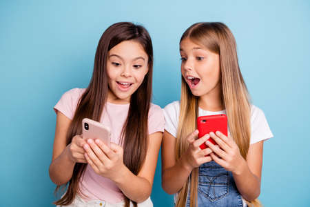 Close up photo two people little she her blond brunette girls having fun long pretty hair telephone hands arms look what I have wearing casual jeans denim t-shirts isolated blue bright background Banco de Imagens