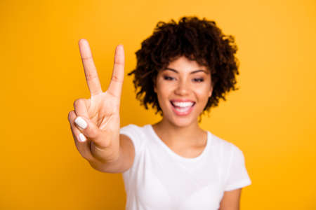 Close up photo beautiful amazed she her dark skin lady glad arms hands fingers raised show v-sign peaceful hippie concept wearing casual white t-shirt isolated yellow bright background