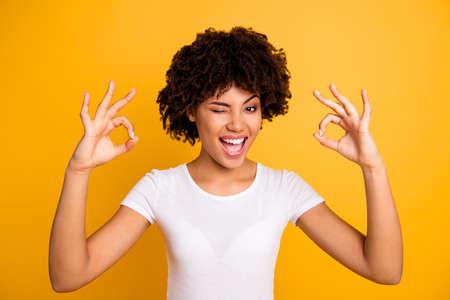 Cerrar foto hermosa increíble ojo guiño ella su piel oscura ondulada dama brazo mano dedos okey símbolo aconsejar comprar comprador probado vistiendo casual camiseta blanca aislado fondo amarillo brillante