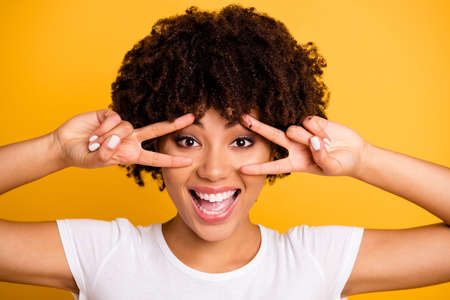 Close up photo beautiful amazed she her dark skin lady glad hands fingers show v-sign peaceful hippie concept open mouth wearing casual white t-shirt isolated yellow bright background Banco de Imagens