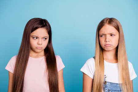 Close-up portrait of two people nice cute lovely attractive charming sad mad offended disappointed gloomy straight-haired pre-teen girls isolated over blue pastel background 版權商用圖片