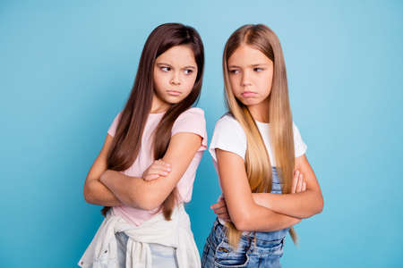 Portrait of two people nice cute lovely attractive sad mad offended gloomy straight-haired pre-teen girls standing back to back folded arms isolated over blue pastel background Stock Photo