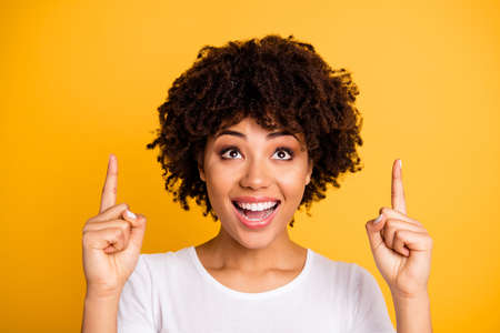 Close-up portrait of her she nice lovely adorable attractive cheerful wavy-haired girl pointing two fingers up isolated on bright vivid shine yellow background Фото со стока