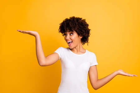 Portrait of her she nice lovely attractive cheerful glad crazy optimistic wavy-haired girl holding two palms copy empty blank space isolated on bright vivid shine yellow background Imagens