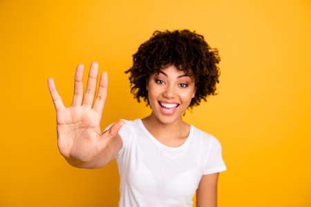 Gros plan photo belle étonnée elle sa peau foncée dame bras mains doigts expliquent un nombre incalculable de cours en classe professeur d'école portant un t-shirt blanc décontracté isolé sur fond jaune clair