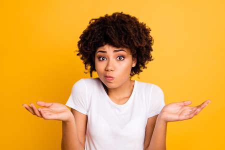 Close-up portret jej ładnej atrakcyjnej zdziwionej nieświadomej falistej dziewczyny pokazującej gest brak informacji na białym tle na jasnym żywym połysku żółtym tle Zdjęcie Seryjne