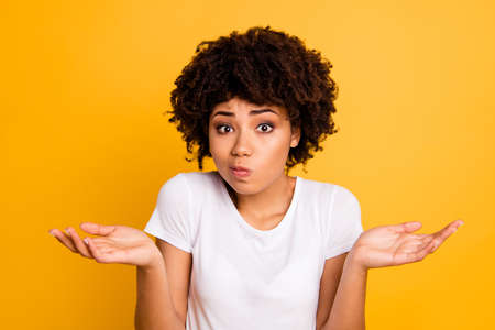 Retrato de primer plano de ella ella agradable atractiva desconcertada ignorante chica de pelo ondulado mostrando gesto sin información aislada sobre fondo amarillo brillante brillante Foto de archivo