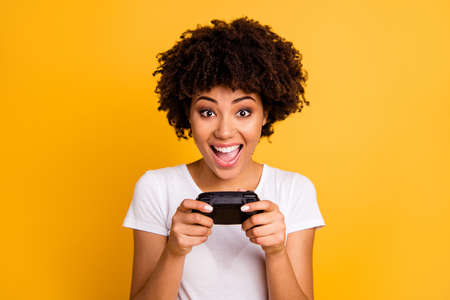 Close-up portrait of her she nice cute attractive charming cheerful cheery wavy-haired lady playing video game free spare time isolated on bright vivid shine yellow background