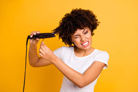 Close up photo beautiful amazing she her dark skin lady curler hands suffering hair curls not making straight struggle wear casual white t-shirt isolated yellow bright vibrant vivid background