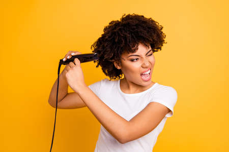 Close up photo beautiful amazing she her dark skin lady curler hands yelling ouch suffer hair curls making straight struggle wear casual white t-shirt isolated yellow bright vibrant vivid background 스톡 콘텐츠